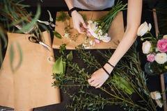Mãos do florista da mulher que criam o ramalhete da flor na tabela Fotos de Stock Royalty Free