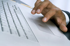 Mãos do homem de negócios em um close up do Touchpad do portátil Fotografia de Stock