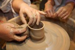 Mãos do potenciômetro criador mestre na roda de oleiro Imagens de Stock