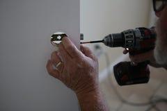 Mãos do ` s do homem usando a broca para reparar o botão de porta Fotos de Stock Royalty Free