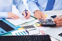 Mãos dos executivos com calculadora. Imagem de Stock