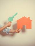 Mãos e casa de papel Abrigando o conceito dos bens imobiliários Fotos de Stock Royalty Free