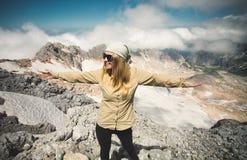 Mãos felizes da jovem mulher levantadas na cimeira Fotografia de Stock Royalty Free