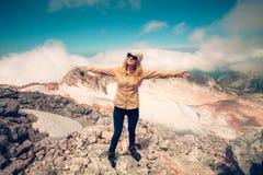 Mãos felizes da jovem mulher levantadas na cimeira Foto de Stock