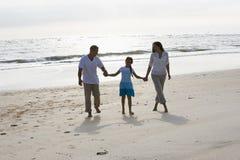 Mãos latino-americanos da terra arrendada da família que andam na praia Imagem de Stock