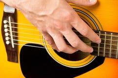 Mãos masculinas que jogam a guitarra acústica, fim acima Fotografia de Stock Royalty Free