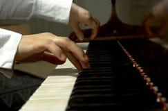 Mãos nas chaves de um piano Fotos de Stock Royalty Free