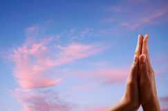 Mãos Praying no fundo do céu Foto de Stock