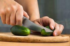 Mãos que cortam o pepino na placa de corte de madeira Imagem de Stock Royalty Free