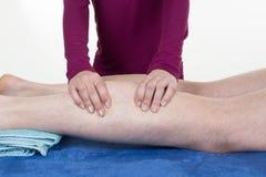 Mãos que fazem massagens o músculo humano da vitela Terapeuta que aplica a pressão na vitela fêmea Fotos de Stock Royalty Free