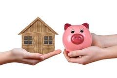 Mãos que guardam a casa de madeira e o mealheiro cor-de-rosa Fotografia de Stock Royalty Free