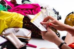Mãos que guardam dólares e bilhete Fotos de Stock