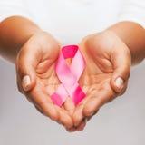 Mãos que guardam a fita cor-de-rosa da conscientização do câncer da mama Imagem de Stock