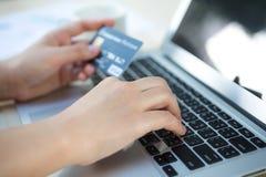 Mãos que guardam um cartão de crédito e que usam o laptop Fotografia de Stock