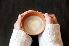 Mãos que guardam a xícara de café com forma do coração Foto de Stock