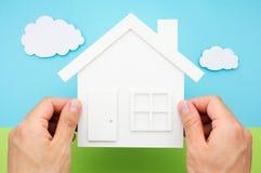 Mãos que mantêm a casa contra o campo do céu e de grama feito do papel Foto de Stock Royalty Free