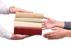 Mãos que passam o montão dos livros Fotografia de Stock Royalty Free