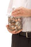 Mãos sênior que prendem o frasco com lotes das moedas Foto de Stock
