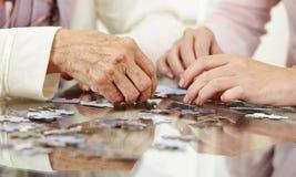Mãos velhas que resolvem o enigma de serra de vaivém Fotos de Stock Royalty Free