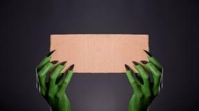 Mãos verdes do monstro com os pregos pretos que guardam a parte vazia de cartão Fotografia de Stock Royalty Free