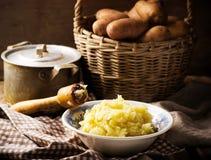 Mosad potatisar och rå potatis i korgen royaltyfri bild