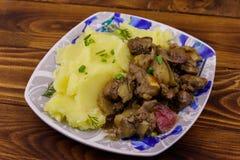 Mosade potatisar med kokt feg lever med äpplet och löken på trätabellen arkivfoto