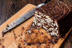 Mosaic Chocolate and Biscuit Cake with knife on wooden surface. Royalty Free Stock Photo