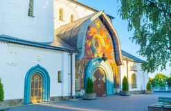 The mosaic entrance of Holy Trinity Cathedral. The Holy Trinity Cathedral of Pochayiv Lavra boasts beautiful mosaic frontage with old styled wooden doors Stock Photo