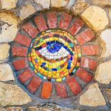 Mosaic Eye of Horus on stone wall. Circular mosaic symbol Eye of Horus on stone wall royalty free stock photo