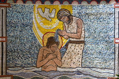 Mosaic Jesus baptism wall. Religious wall decorated with mosaic tiles depicting Jesus performing a baptism in a river with a white dove overhead Stock Photo