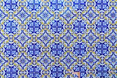 Mosaic of Portuguese azulejo tiles. Repeated pattern of traditional Portuguese azulejo tiles - blue, yellow and white close-up, frontal parallel view stock photo
