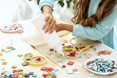 Mosaic puzzle art for kids, children`s creative game. The mosaic puzzle art for kids, children`s creative game. The hands are playing mosaic at table. Colorful Stock Photo