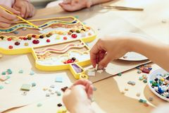 Mosaic puzzle art for kids, children`s creative game. The mosaic puzzle art for kids, children`s creative game. The hands are playing mosaic at table. Colorful Royalty Free Stock Photos