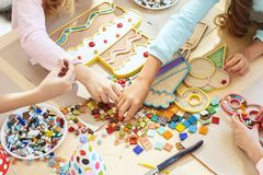 Mosaic puzzle art for kids, children`s creative game. two sisters are playing mosaic. The mosaic puzzle art for kids, children`s creative game. The hands are Royalty Free Stock Image