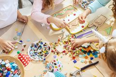 Mosaic puzzle art for kids, children`s creative game. two sisters are playing mosaic. The mosaic puzzle art for kids, children`s creative game. The hands are Royalty Free Stock Photography