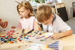 Mosaic puzzle art for kids, children`s creative game. two sisters are playing mosaic. The mosaic puzzle art for kids, children`s creative game. The hands are Royalty Free Stock Photo