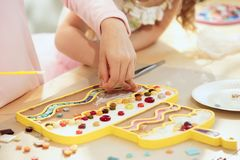Mosaic puzzle art for kids, children`s creative game. The mosaic puzzle art for kids, children`s creative game. The hands are playing mosaic at table. Colorful Royalty Free Stock Images