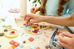 Mosaic puzzle art for kids, children`s creative game. The mosaic puzzle art for kids, children`s creative game. The hands are playing mosaic at table. Colorful Stock Image