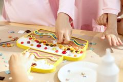 Mosaic puzzle art for kids, children`s creative game. The mosaic puzzle art for kids, children`s creative game. The hands are playing mosaic at table. Colorful Royalty Free Stock Photo