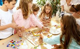 Mosaic puzzle art for kids, children`s creative game. The mosaic puzzle art for kids, children`s creative game. The hands are playing mosaic at table. Colorful Stock Photos