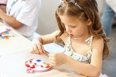 Mosaic puzzle art for kids, children`s creative game. two sisters are playing mosaic. The mosaic puzzle art for kids, children`s creative game. The hands are Stock Photo