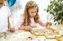 Mosaic puzzle art for kids, children`s creative game. two sisters are playing mosaic. The mosaic puzzle art for kids, children`s creative game. The hands are Stock Images