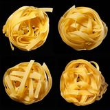 Mosaic of raw uncooked tagliatelle nests on black background. Top view. Traditional Italian pasta. Mosaic of raw uncooked tagliatelle nests on black background stock photos