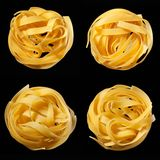Mosaic of raw uncooked tagliatelle nests on black background. Top view. Traditional Italian pasta. Mosaic of raw uncooked tagliatelle nests on black background royalty free stock images
