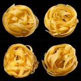 Mosaic of raw uncooked tagliatelle nests on black background. Top view. Traditional Italian pasta. Mosaic of raw uncooked tagliatelle nests on black background royalty free stock image