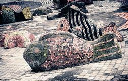 Mosaic sculptures of fish near the pond. stock photo