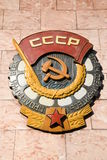 Soviet CCCP emblem with hammer and sickle. Mosaic soviet CCCP emblem with hammer and sickle hanging on a rock wall royalty free stock images
