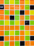 Mosaic tile background. Fragment of tile with orange, yellow, black and green squares Royalty Free Stock Photography