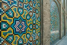 Mosaic traditional floral wall and old door. Mosaic traditional oriental floral wall pattern in Iran stock photo