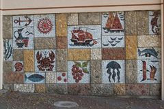 Mosaic on the wall under the open sky. Panel with paintings of marine subjects, objects and animals.Mosaic of natural stones and tiles Royalty Free Stock Image